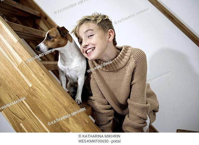 Portrait of grinning boy and his Jack Russel Terrier on stairs at home