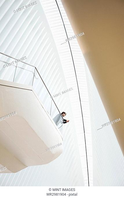 View from below of a man standing on a balcony in the Oculus building on his phone, leaning on the railing. Large ribbed roof arch above him