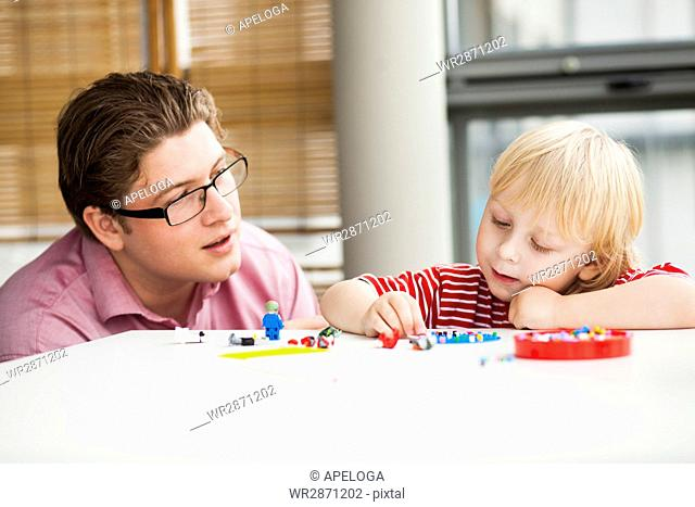 Father looking at boy playing with toys on table