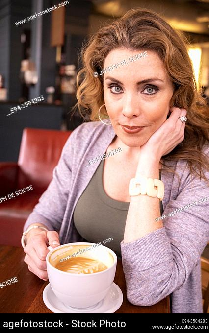 A pretty 37 year old redhead woman in a holding a large cup of coffee in a cafe