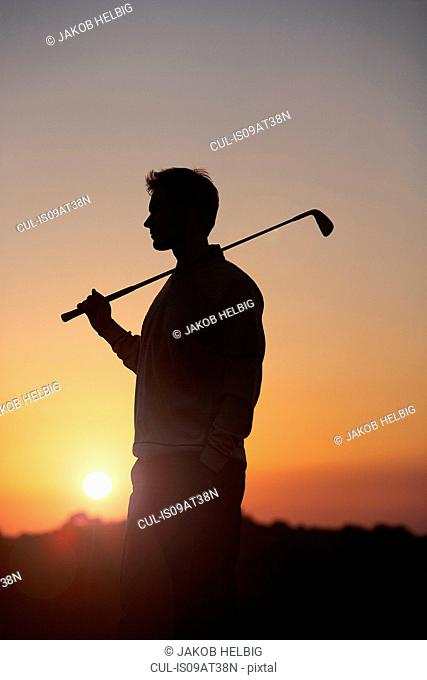 Golfer carrying golf club over shoulder in front of sunset, looking away