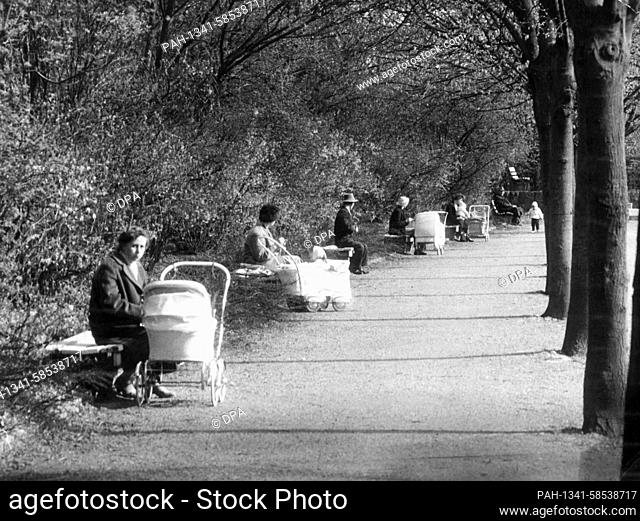 Passers-by and mothers with prams enjoy the warm sunshine in a park somewhere in Germany on 5 May 1960. | usage worldwide. - /Germany