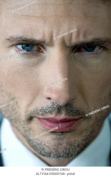 Businessman glaring with furrowed brow, portrait