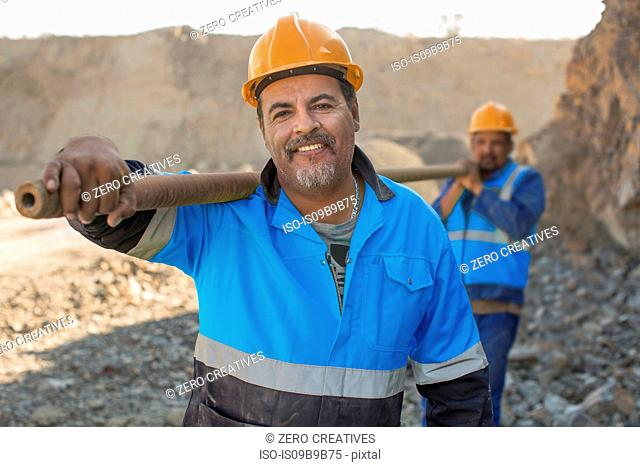Portrait of quarry workers in quarry, carrying metal pipe