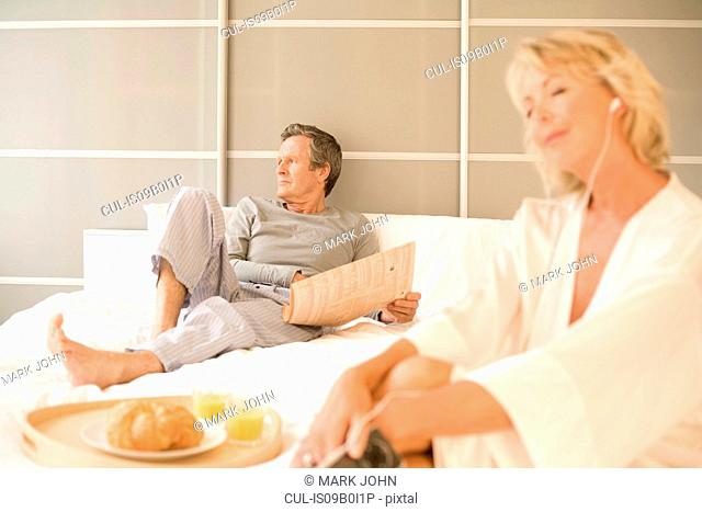 Couple relaxing on bed reading newspaper and listening to earphones