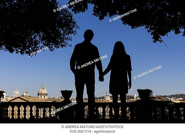 Silhouette couple holding hands overlooking the city of Rome Italy