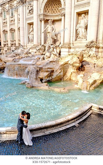 Married couple kissing by Fontana di Trevi in Rome Italy