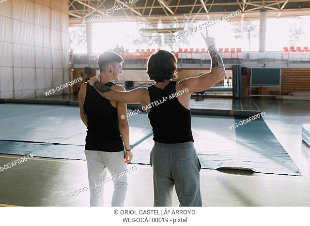 Rear view of two happy gymnasts standing in gym