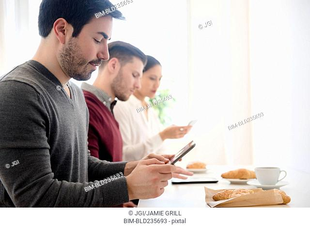 Business people using technology at breakfast table