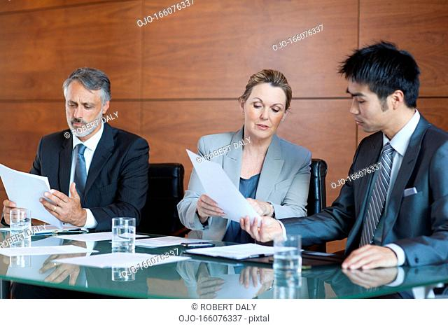 Businesswoman showing paperwork to businessman in meeting