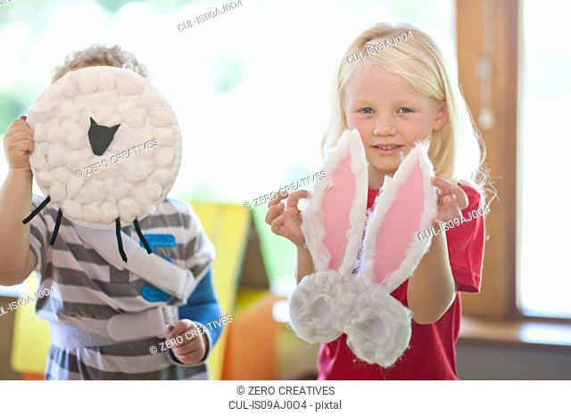 Boy and girl holding up sheep and rabbit creations at nursery school