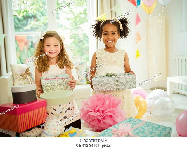 Portrait smiling girls holding birthday gifts