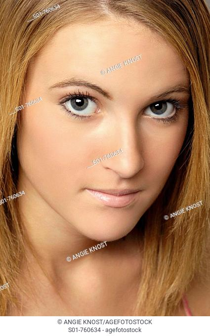 This stock photo shows a close up view of a young woman's face  She has clear skin and is making eye contact