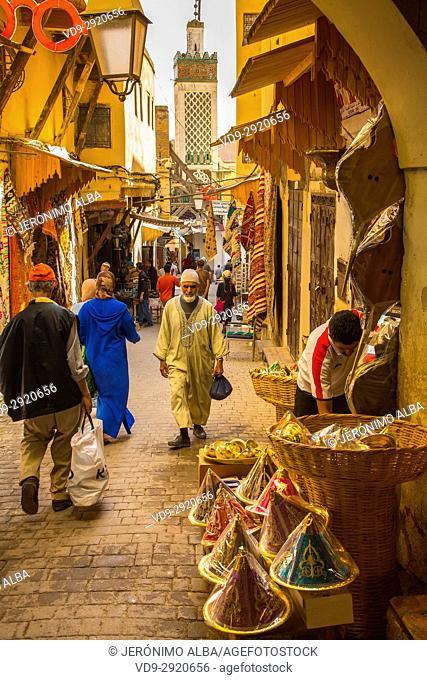 The Medersa Bou Inania minaret. Street life scene. Souk Medina of Fez, Fes el Bali. Morocco, Maghreb North Africa