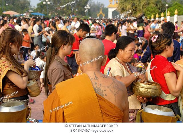 Theravada Buddhism, That Luang Festival, Tak Bat, tattoos, monk with spiritual tattoos on his back and bald head, believers, pilgrims giving alms, orange robes