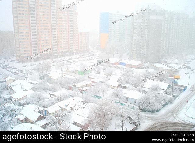 Winter snowfall in residential area with contrast of urban modern apartment buildings and old private house, Kiev, Ukraine