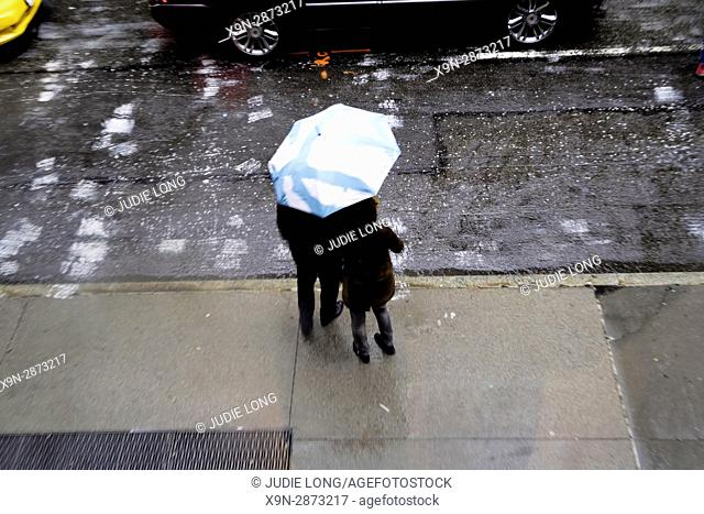 New York City, Manhattan. Man and Woman Standing Under an Umbrella on a RAiny Day, Trying to Hail a Taxi Cab