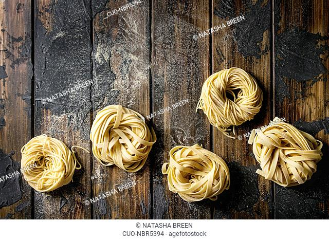 Variety of italian homemade raw uncooked pasta spaghetti and tagliatelle with semolina flour over dark plank texture wooden table