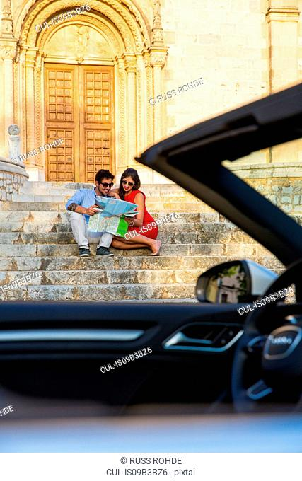 Young couple with convertible sitting on church stairway looking at map, Calvia, Majorca, Spain