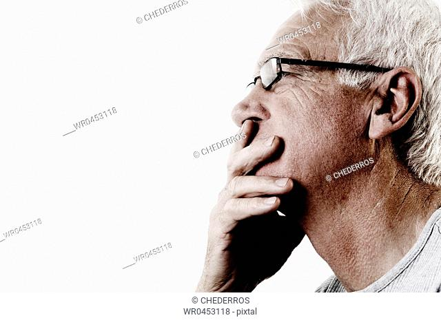 Close-up of a senior man thinking with his hand over his mouth
