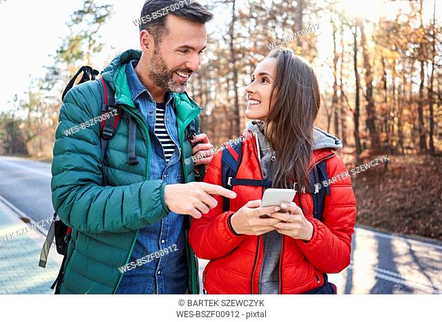 Happy couple checking smartphone on a road in the woods during backpacking trip