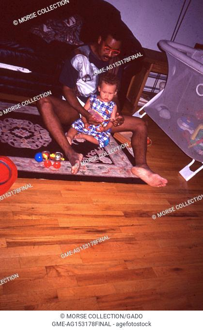 View of an African American man reading a book to a young African American child, July, 1995. The little girl and man sit together on the floor of a family...