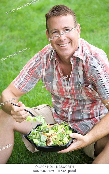 Portrait of a mature man holding a bowl of salad and smiling