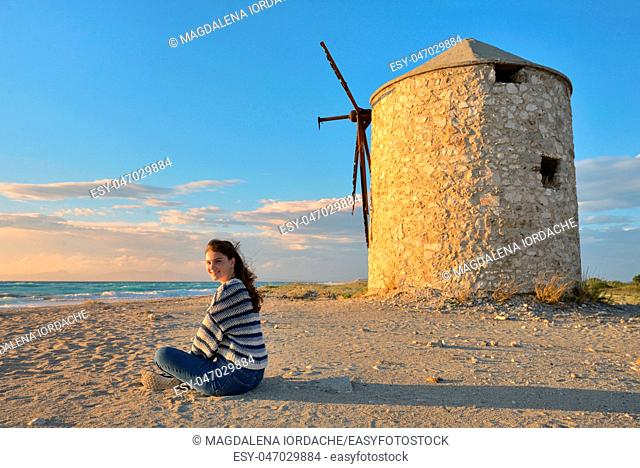 Teen girl and Old windmill ai Gyra beach, Lefkada