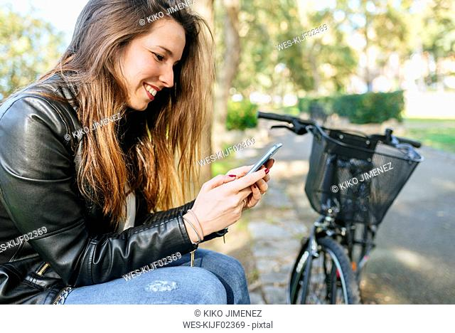 Young woman with bicycle sitting in park using cell phone