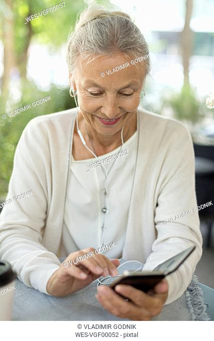 Smiling senior woman at an outdoor cafe with cell phone and earphones