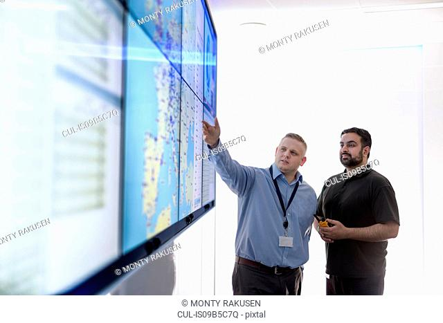 Operators in automotive emergency response control room in car factory