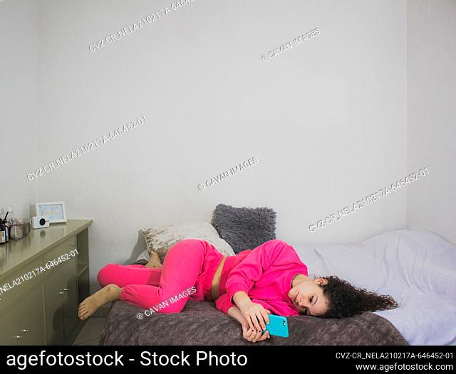 woman in bed watching social media on mobile