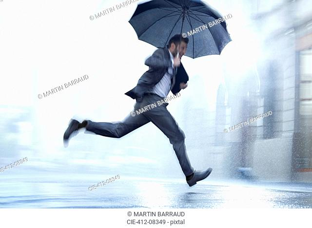 Businessman running with umbrella in rainy street