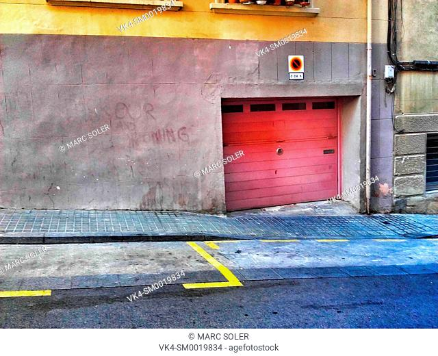 Red metal garage gates with no parking road sign. Barcelona, Catalonia, Spain