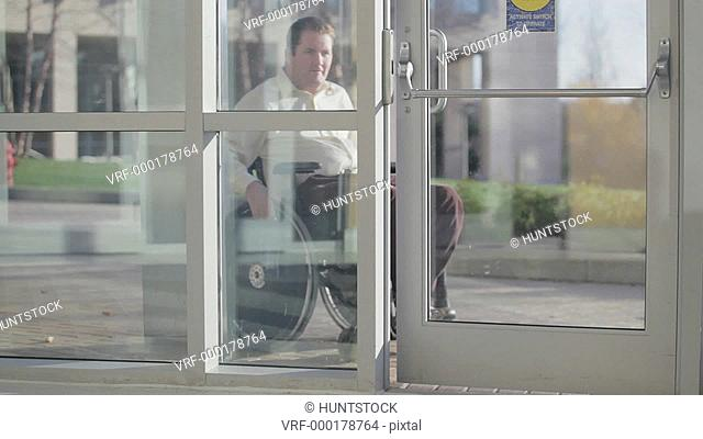 Man with spinal cord injury in wheelchair using automatic door opener to enter two doors of building