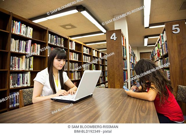 Woman on laptop and girl on video game in library