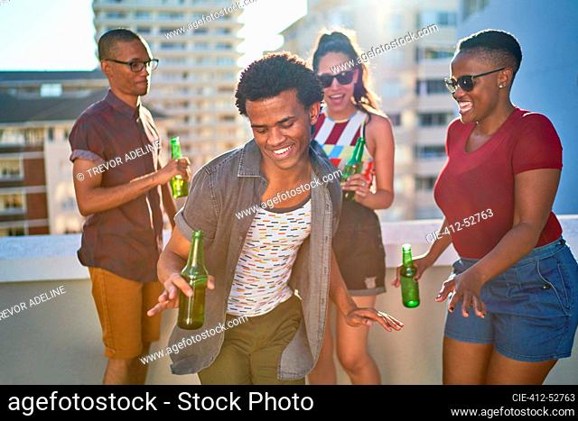 Carefree young friends drinking beer on sunny urban rooftop