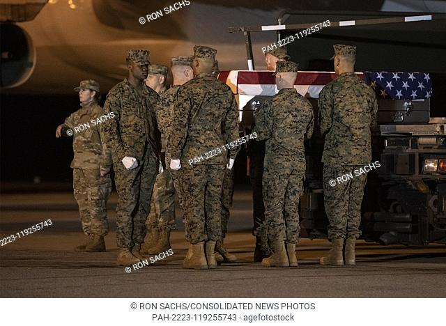 A United States Marine Corps carry team participates in the Dignified Transfer of the transfer case containing the remains of United States Marine Corps Staff...