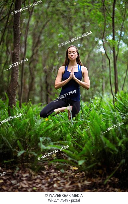 Woman performing yoga in forest