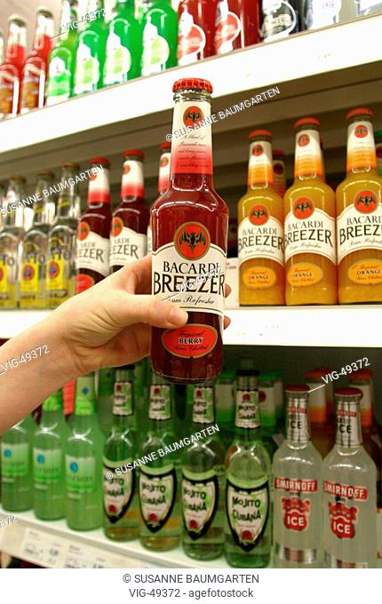 Hand is taking a bottle Bacardi Breezer / Tropical Berry ( Bacardi rum with fruit juice ) out of a supermarket shelfes with alcoholic mix drinks