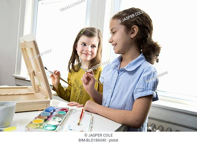 Smiling girls painting