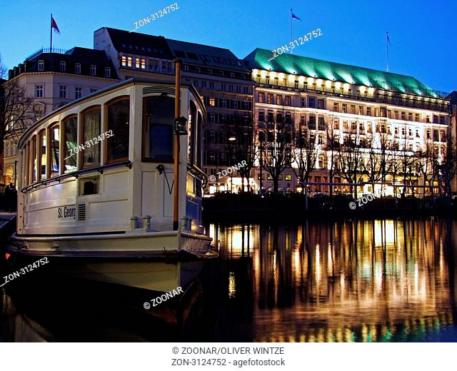 Blick vom Anleger am Jungfernstieg auf den Alsterdampfer Sankt Georg und das Hotel Vier Jahreszeiten während der blauen Stunde / View from the jetty at...