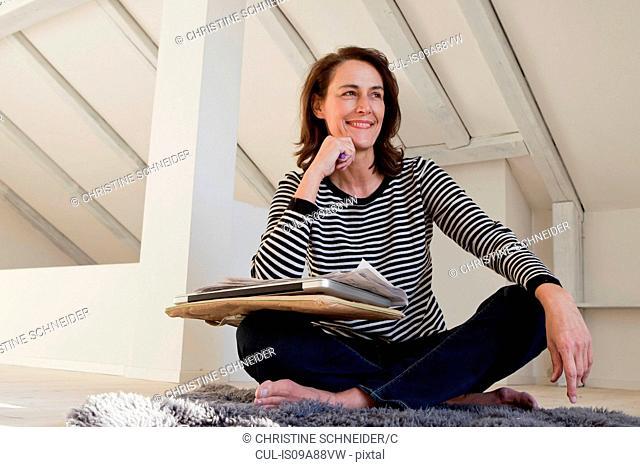 Portrait of woman wearing striped top sitting cross legged