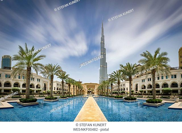 United Arab Emirates, Dubai, Burj Khalifa with traditional styled houses around a water basin with palm trees