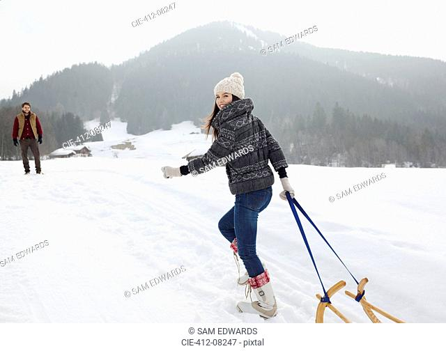 Portrait of smiling woman pulling sled in snowy field