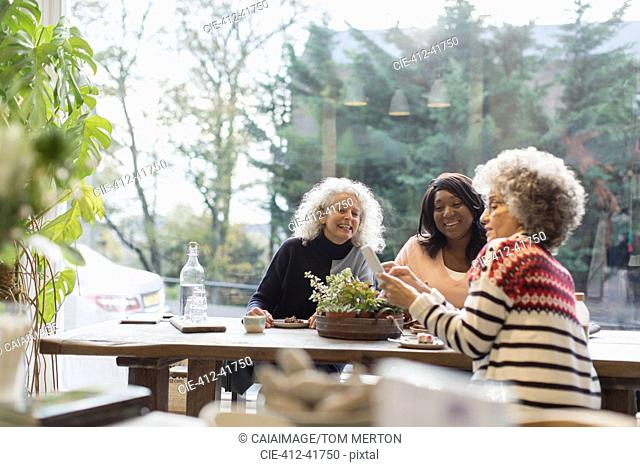 Smiling women friends using smart phone at cafe table