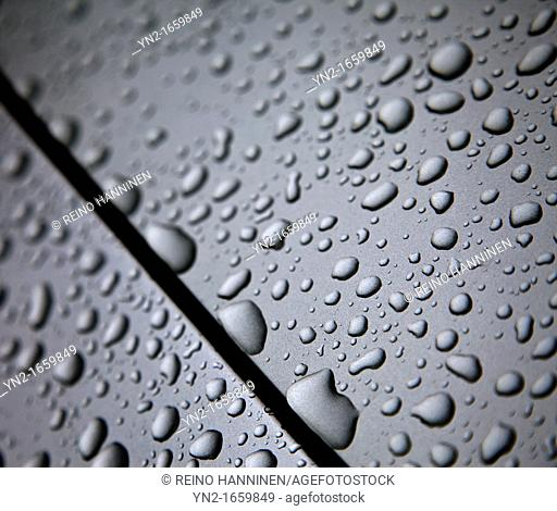 Closeup of water drops on grey silver colored car