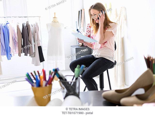 Portrait of female costume designer using mobile phone in studio
