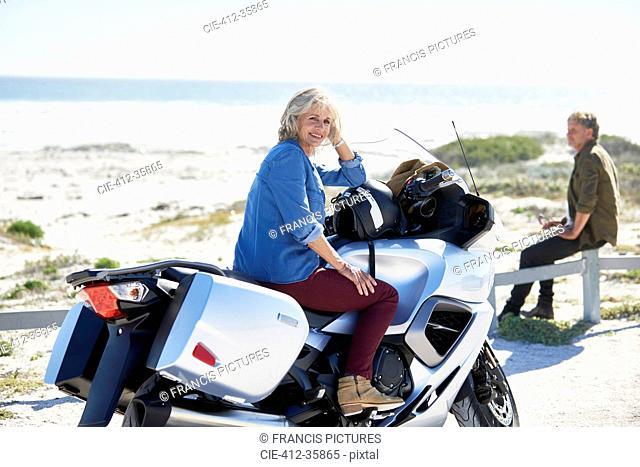 Portrait confident senior woman on motorcycle on sunny beach