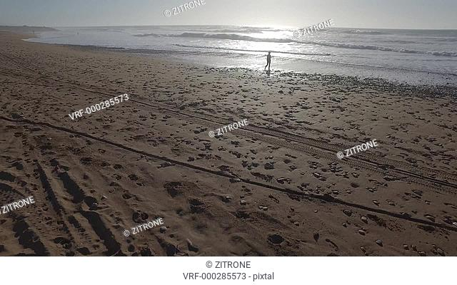 Drone footage of woman walking on beach during sunset